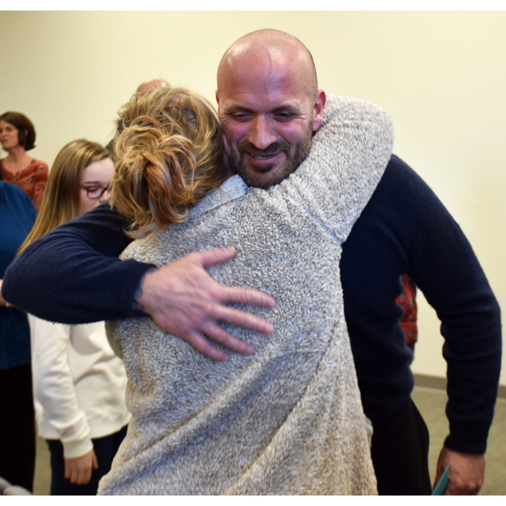 Christopher Ruggles receives a congratulatory hug at his graduation from the Merrimack County Drug Court in Concord on January 28. He was the first person to graduate from the program.